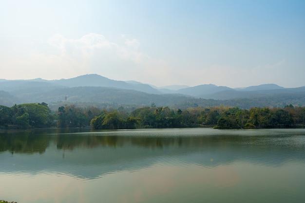 Landschaftsseeansichten an der ang kaew chiang mai university im verschmutzungsnebel im naturwald bergstaubluftverschmutzung bei 2,5 oder kleinpartikel pm 2,5 mikrometer hintergrund mit weißer wolke in thailand
