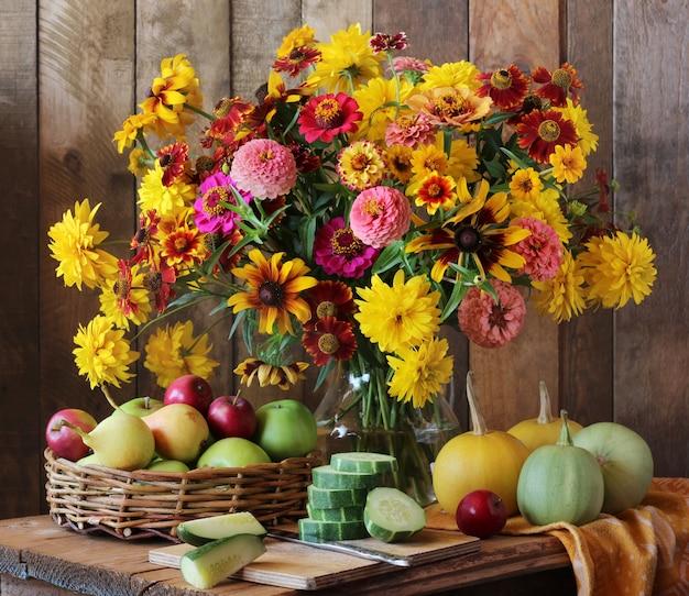 Landstillleben mit gartenblumen, -gemüse und -frucht auf dem tisch.