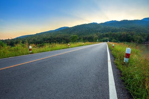 Landstraße mit szenischer ansicht des reservoirs huay tueng tao mit gebirgszugwald