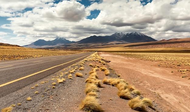 Landstraßenstraße, trockenes gras und vulkan in atacama-wüste in chile mit gelber und blauer landschaft