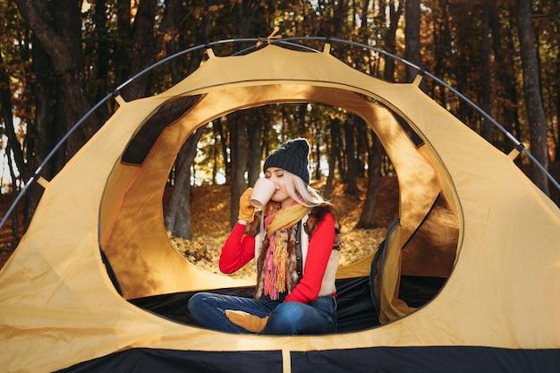 Landtourismus. dame, die im zelt sitzt und heißen tee im herbstnaturpark trinkt.