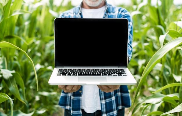 Landwirt auf dem gebiet, das laptopbildschirm zeigt