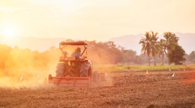 Landwirt auf großem traktor im land, zum des bodens vorzubereiten