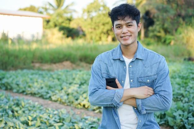 Landwirt (besitzer) mann, der arm kreuzt und in der erntezeit auf landwirtschaftlichem feld steht