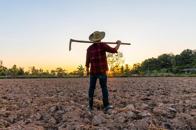 Landwirt, der an feld bei dem sonnenuntergang im freien arbeitet