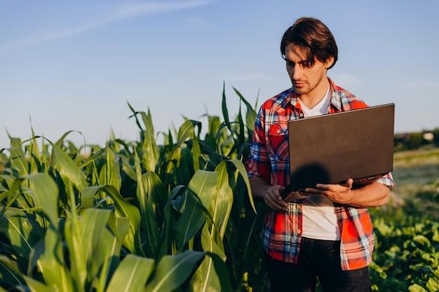 Landwirt, der auf einem gebiet hält offenen laptop steht und eine ertragskontrolle übernimmt