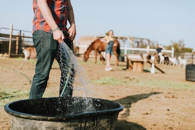 Landwirt, der eine wanne mit wasser füllt