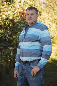 Landwirt, der im apfelgarten steht