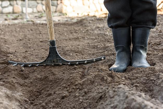 Landwirt, der im garten mit rechenausgleichsgrund arbeitet. vorbereitung des bodens zum pflanzen.