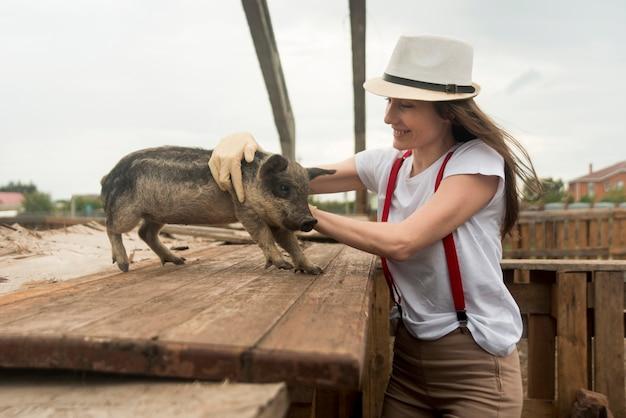 Landwirt, der um schweinen in einem schweinestall sich kümmert