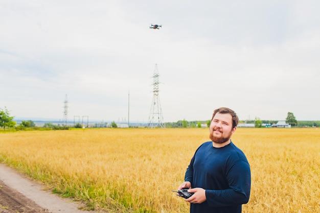Landwirt hält fernbedienung mit seinen händen, während quadcopter auf hintergrund fliegt. drohne schwebt hinter dem agronomen auf dem weizengebiet. landwirtschaftliche neue technologien und innovationen. rückansicht.