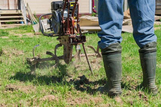 Landwirt in gummistiefeln und blue jeans pflügt einen boden mit kleinem motortraktor.