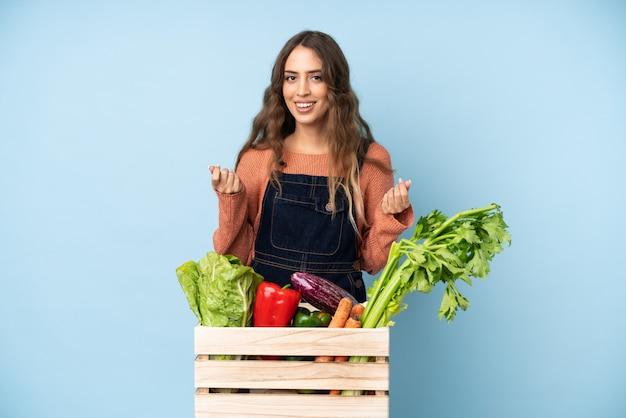 Landwirt mit frisch ausgewähltem gemüse in einem kasten, der geldgeste verdient