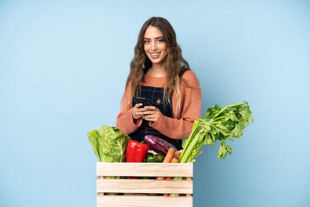 Landwirt mit frisch gepflücktem gemüse in einer box, die eine nachricht mit dem handy sendet
