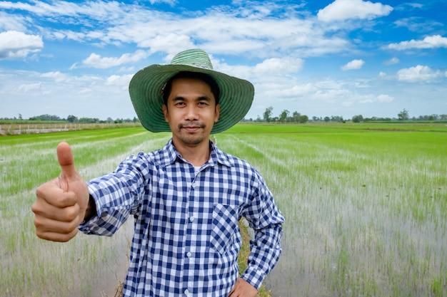 Landwirt mit weißem bartdaumen herauf den asiatischen mann, der in einem hemd steht und kamera betrachtet