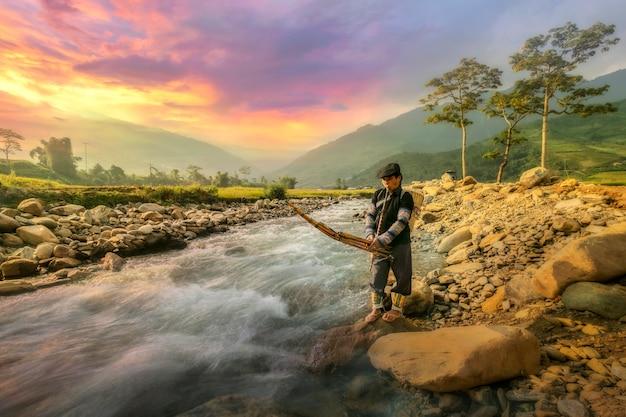 Landwirt mittleren alters, der ein musikinstrument spielt am rande des baches auf dem lande im norden vietnams