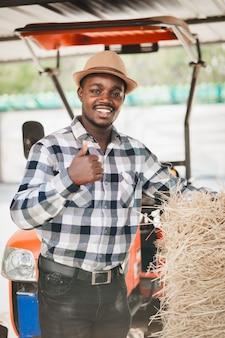 Landwirt stehend mit reisstrohballen und traktor. landwirtschafts- oder anbaukonzept