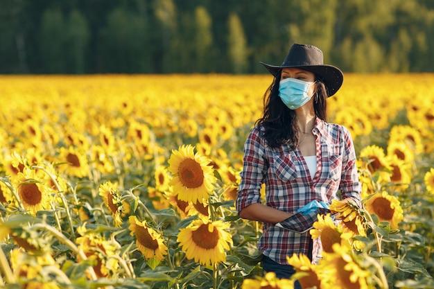 Landwirtin agronomin in handschuhen und gesichtsmaske auf dem sonnenblumenfeld mit tablette, die die ernte überprüft
