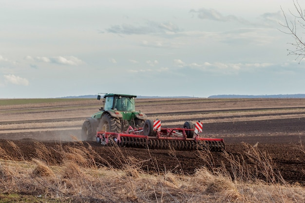 Landwirtschaft, traktor, der land mit saatbettgrubber als teil der vorsaataktivitäten im frühjahr der landwirtschaftlichen arbeiten auf ackerland vorbereitet
