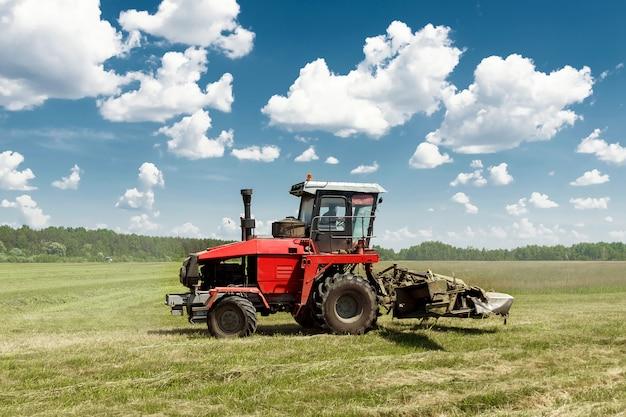 Landwirtschaftliche maschinerie, erntemaschine, die gras auf einem gebiet gegen einen blauen himmel mäht.
