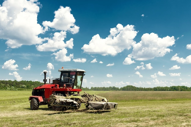 Landwirtschaftliche maschinerie, erntemaschine, die gras auf einem gebiet gegen einen blauen himmel mäht