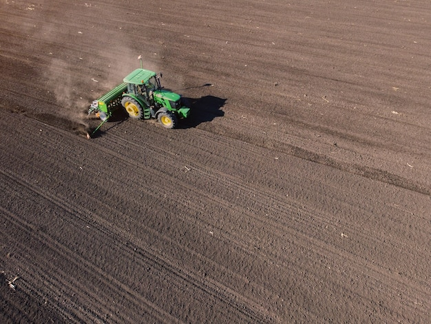Landwirtschaftlicher traktor pflügt bodenfeld zur aussaat