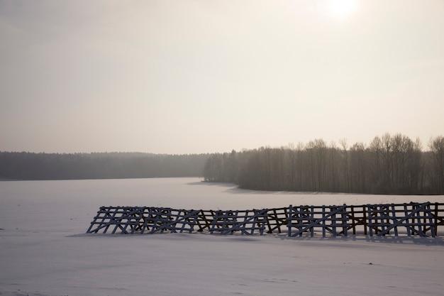Landwirtschaftliches feld während des sonnenuntergangs in der wintersaison, das feld hat einen holzzaun, um den schnee zu halten und wasser während des auftauens zu bekommen