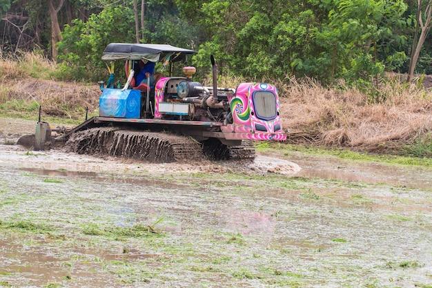 Landwirtschaftsackerland, traktor mit dem pflug, der ein bodenfeld pflügt