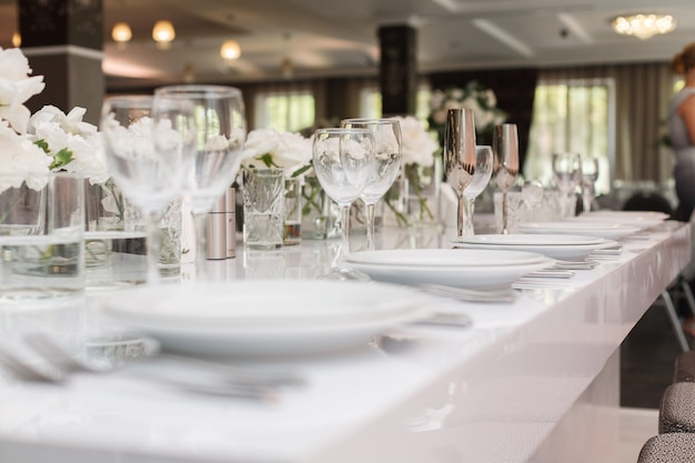 Lang gedienter festtisch mit gläsern, tellern und besteck. festlich gedeckter tisch zur geburtstags- oder hochzeitsfeier im restaurant. innenraum des bankettsaals im café. ort der feier