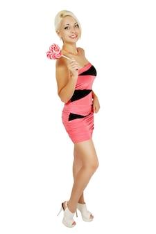 Langbeinige blondine in einem rosa kleid mit einer herzförmigen süßigkeit