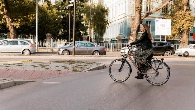 Lange ansicht der frau, die das fahrrad reitet