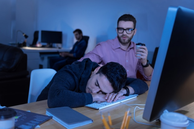 Lange arbeiten. müder, erschöpfter, gut aussehender mann, der am tisch sitzt und während langer arbeitszeiten auf der tastatur schläft