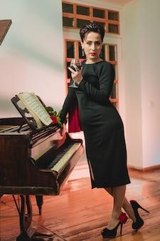 Lange aufnahme einer stilvollen und modischen eleganten frau, die zu hause neben dem klavier für die kamera posiert und weinglas hält holding