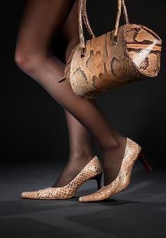 Lange beine in schlangenlederschuhen mit handtasche über schwarz