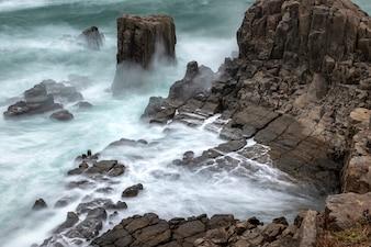 Lange Belichtung von den Wellen, die das Seeufer schlagen. Tojinbo Cliff, Präfektur Fukui, Japan