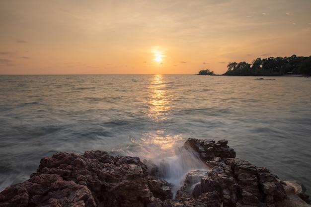 Lange belichtungen twilight sonnenuntergang und meereswellen schlagen die felsen