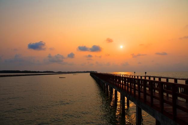 Lange brücke am seeansicht auf morgenmeerblick-sonnenaufganghintergrund