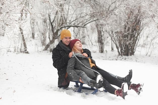 Lange einstellung eines paares, das auf einem schlitten im schnee sitzt