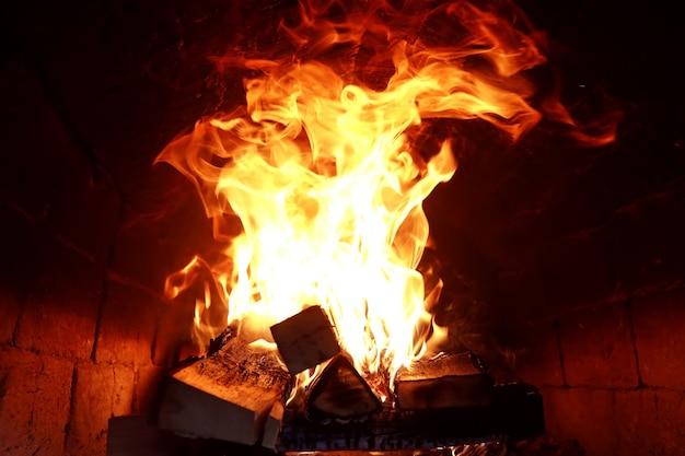 Lange flammenzungen von brennendem feuer in einem steinofen
