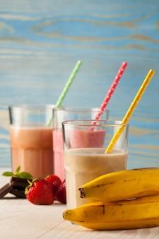 Lange gläser milchshakes mit schokolade, erdbeere, banane, mit eis auf weiß