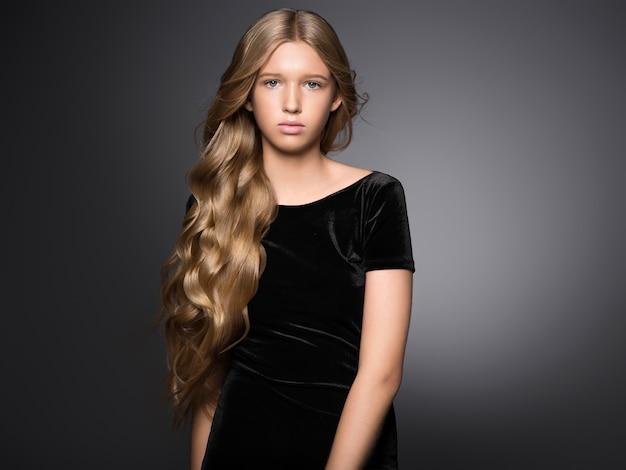 Lange haare schönheit mädchen gesunde lockige lange frisur blondine im schwarzen kleid. studioaufnahme.