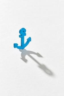 Lange harte schatten auf einem hellgrauen von kleinen blauen plastikankerspielzeug mit kopierraum.