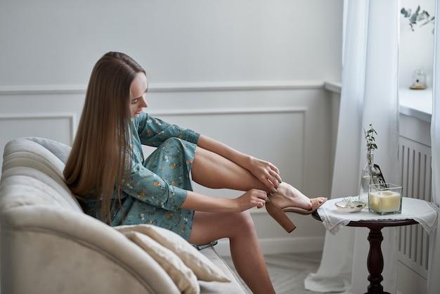 Lange nackte frauenbeine in beigefarbenen sandalen mit hohen absätzen nahaufnahme von befestigungsschuhen