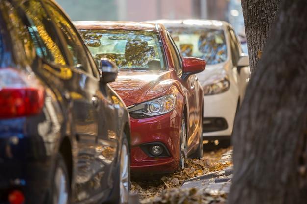 Lange reihe verschiedener glänzender autos und lieferwagen, die am sonnigen herbsttag am leeren straßenrand auf verschwommenem grünem goldenem laub geparkt wurden