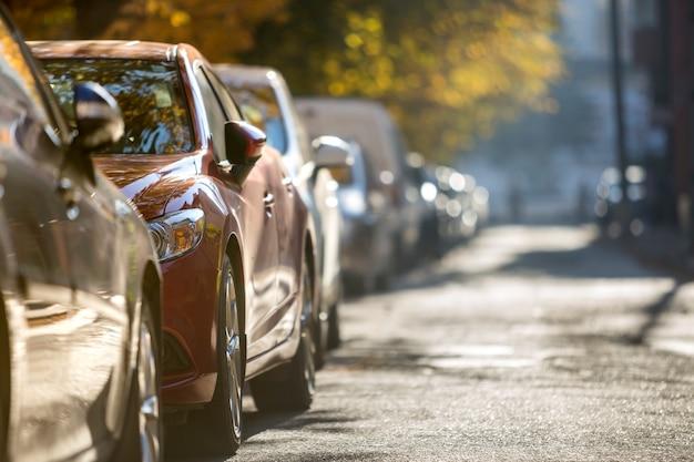 Lange reihe von verschiedenen glänzenden autos und lieferwagen, die entlang des leeren straßenrandes am sonnigen herbsttag auf verschwommenem grünem goldenem laub-bokehhintergrund geparkt werden.