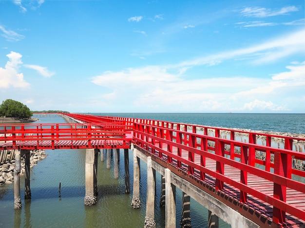 Lange rote brücke überqueren sommerstrand gegen blauen himmelhintergrund bei samutsakhon provinz, thailand.