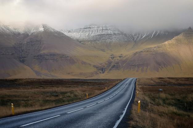 Lange schmale straße mit schönen hügeln und bergen, die mit nebel bedeckt sind