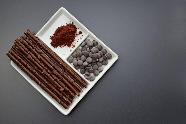 Lange schokoladenstangen, schokoladenknöpfe und kakaopulver in einer quadratischen platte auf grauem hintergrund. Premium Fotos