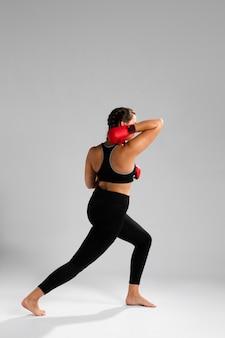 Lange sicht der frau mit boxhandschuhen
