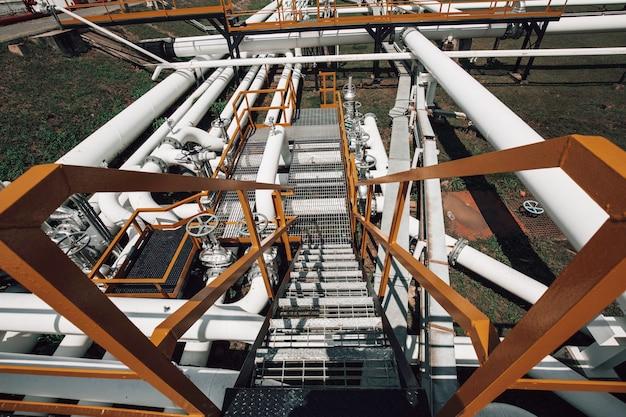 Lange stahlrohre und flansch in der rohölfabrik während der raffinerie petrochemieindustrie in der gasbrennerei